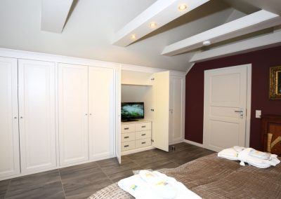 Das Schlafzimmer mit Balkon und einem Flachbildschirm