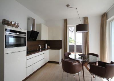 Die moderne Küche mit gemütlichen Lederstühlen vor dem Fenster mit Meerblick