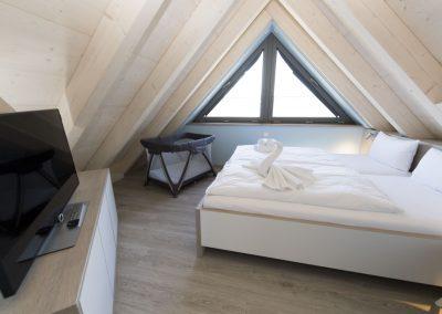 Das 4. Schlafzimmer mit Doppelbett und Kinderbett im Dachgeschoss