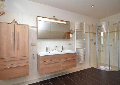 Das Vollbad mit Dusche, Eckbadewanne und Handtuchheizkörper.