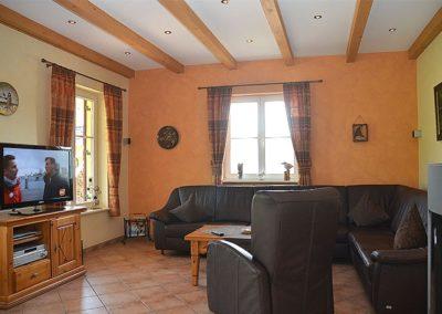 Das Wohnzimmer mit gemütlichem Ledersofa und Flachbildschirm.