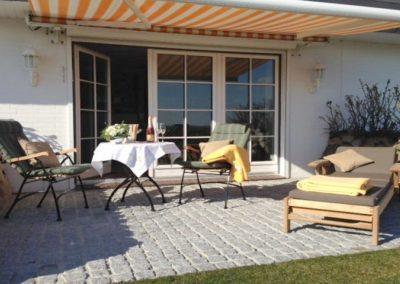 Die Terrasse mit exklusiven Gartenmöbeln von Garpa und einer Markise