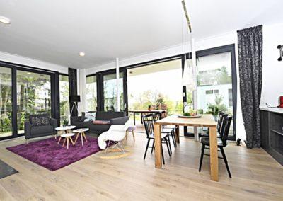 Ein großer Esstisch ist zwischen der Küche und dem Wohnbereich platziert.