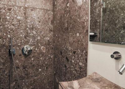 Das zweite Luxusbad ist ebenso mit einer Regendusche und Marmor versehen