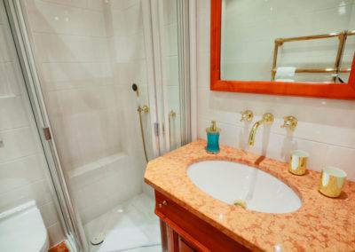 Edle Materialien und goldene Armaturen schmücken das Bad