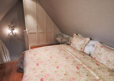 Ein großes Doppelbett und ein Kleiderschrank im Dachgeschoss