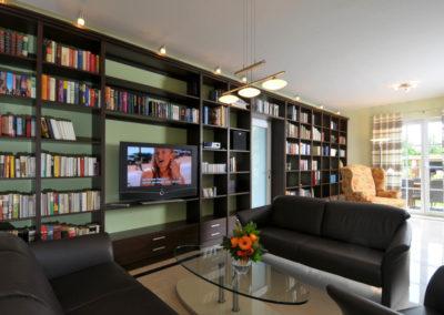 Neben einem Loewe- Flatscreen dienen zahlreiche Bücher der Unterhaltung.
