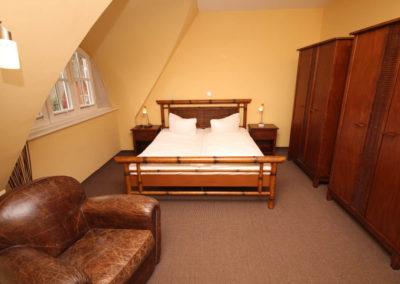 Ein Schlafzimmer mit Doppelbett und Flatscreen im Obergeschoss.