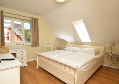 Schlafzimmer mit Doppelbett und Schreibtisch im Obergeschoss.