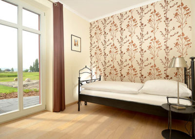 Ein Schlafzimmer mit Einzelbett und Terrassenzugang im Erdgeschoss.