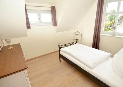 Ein Schlafzimmer mit Einzelbett im Obergeschoss.