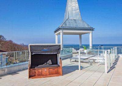 Gartenmöbel, Sonnenliegen und ein Strandkorb stehen auf der Dachterrasse bereit.