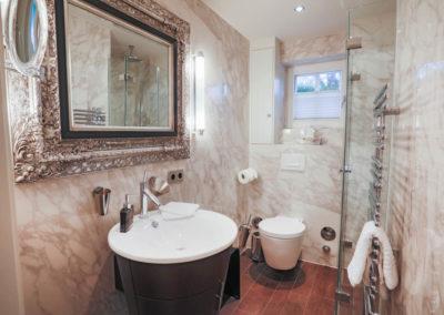 Das Duschbad ist eingebettet in weißem Marmor