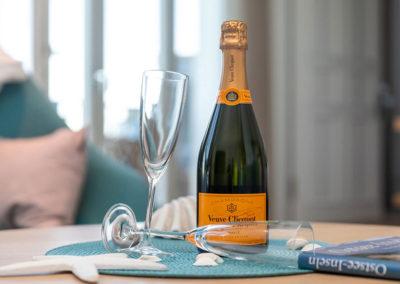 Stossen Sie an auf Ihren wohlverdienten Urlaub mit einem Glas Champagner.