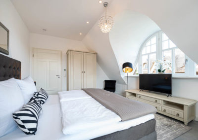 Das zweite Schlafzimmer mit Doppelbett und Flachbildschirm.