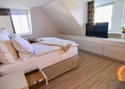 Masterbedroom mit Flatscreen, der auf Knopfdruck im Sideboard versinkt.