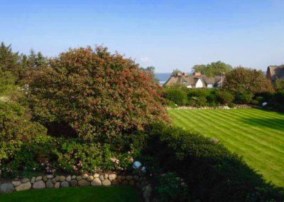 Der Garten ist umrahmt von Meterhohen Bäumen, Sträuchern und Hecken samt Kugelleuchten.