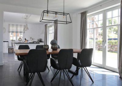 Der große Esstisch mit Polsterstühlen befindet sich zwischen Küche und Wohnbereich.