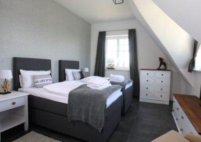 Ein Schlafzimmer ist mit zwei Einzelbetten eingerichtet.