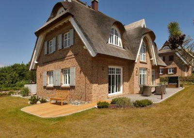 Zwei mit Holz ausgelegte Terrassen sind mit Gartenmöbel bestückt.