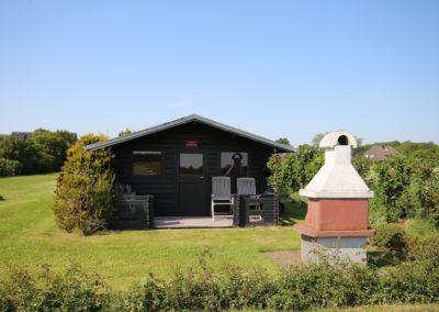 Ein Grillhaus mit Gartenmöbel, Spüle und Kühlschrank